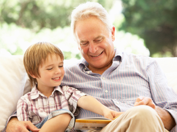Grandfather With Grandson Reading Together On Sofa
