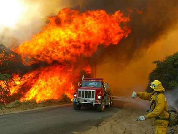 Los Angeles County firefighter Bruce Alpern, right, directs colleague Todd Fischer out of the path Tuesday, July 13, 2004, of wind-driven flames along Pine Canyon Road near Lake Hughes in Northern Los Angeles County. Hot temperatures and erratic winds spread a wildfire in Angeles National Forest near Lake Hughes to more than 3,000  acres.  (AP Photo/The Los Angeles Times, Bryan Chan) ***MANDATORY CREDIT: Bryan Chan/Los Angeles Times***