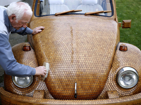 Bosnian pensioner Momir Bojic cleans his wooden Volkswagen Beetle car in front of his home in Celinac near Banja Luka, April 2, 2014. Bojic,71, an avid Volkswagen fan, created the car from over 50,000 separate pieces of oak and took two years to complete it. German carmaker Volkswagen posted a quarterly jump in operating profit as Europe's fledgeling economic recovery lifted sales of Audi and Porsche luxury models to record levels. First-quarter underlying earnings at Europe's biggest carmaker gained 22 percent to 2.9 billion euros ($4 billion), compared with 2.3 billion a year ago, VW said on April 29, 2014. Picture taken April 2, 2014. REUTERS/Dado Ruvic (BOSNIA AND HERZEGOVINA - Tags: TRANSPORT BUSINESS SOCIETY)